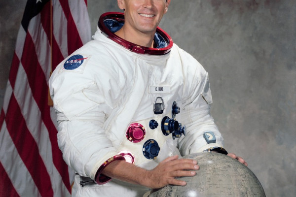 Portrait of Astronaut Charles M. Duke Jr., in space suit with a lunar globe in front of him and an American flag behind him. NASA Photo ID: S71-51289 Source: http://spaceflight.nasa.gov/gallery/images/apollo/apollo16/html/s71-51289.html
