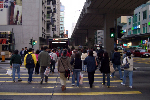 Pedestrians cross a road in Mong Kok.