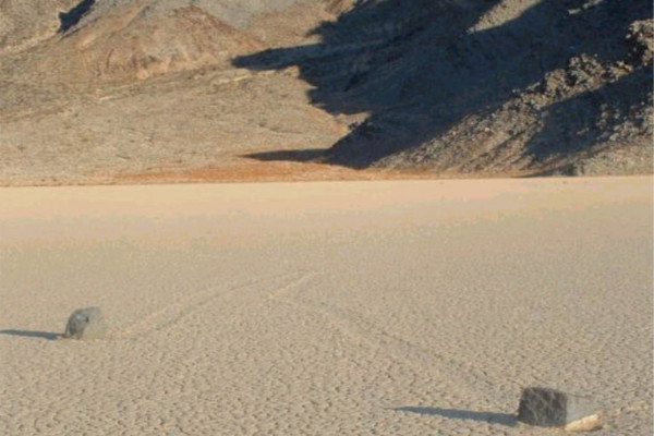 Picture of two rocks on Racetrack Playa in Death Valley. Notice the mysterious groves leading away from the stones.