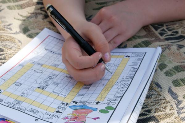 Person solving Finnish crossword puzzle
