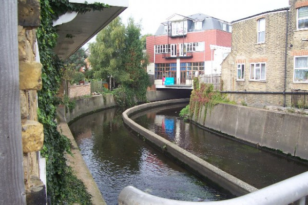River Wandle, Strathville Rd, SW18. From a road bridge, with some new flats built over the river.
