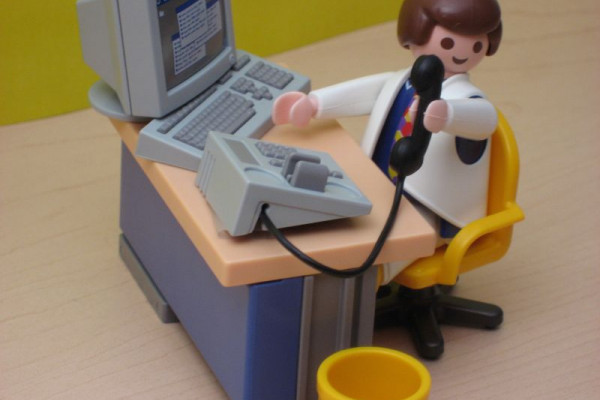 A Playmobil man sitting at a desk