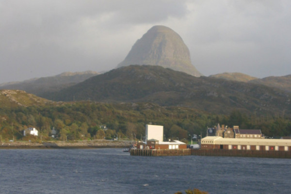 Suilven Caisteal Liath above Lochinver. The 'sugar loaf' Caisteal Liath buttress of Suilven dominates the skyline above Lochinver. This view over the fishing port was taken from the Baddidarach side of Loch Inver. The ornate building by the harbour...