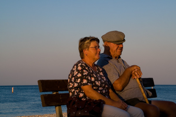 An elderly couple sitting together looking out to sea