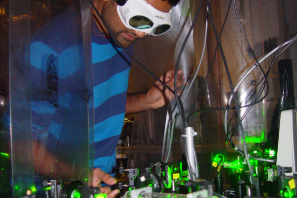 Dr Dhiren Kara adjusting the laser system used to measure the shape of the electron.