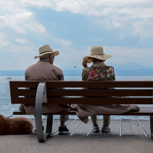 Two people on a bench by the sea