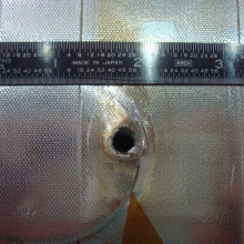 Image of the entry hole created on Space Shuttle Endeavour's radiator panel by the impact of unknown space debris.