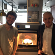 this is a picture of 2 men standing next to an oven