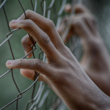 Hands on a fence
