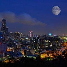 A moon rising over a cityscape