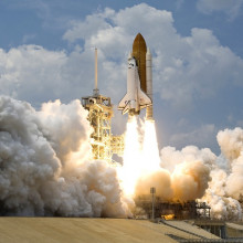 A rocket, with space shuttle attached, blasting off from Earth