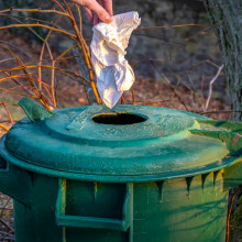 Throwing away a paper towel in a bin.