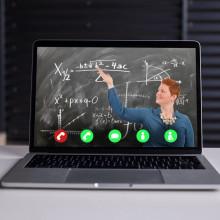 image of teacher next to blackboard, via video call