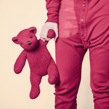 person in pink pyjamas holding pink teddybear