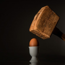 A wooden mallet about to smash an egg in a teacup