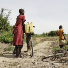 Three children walking bikes on a dirt road in Uganda.