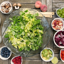 A plate of salad, surrounded by bowls of various fruits