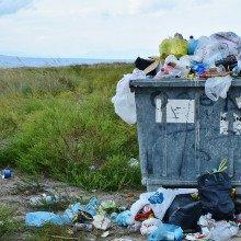 An overflowing rubbish bin in a field.