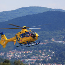 A yellow helicopter in flight above a mountainous region.