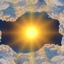 The sun shining through a stylised hole in some clouds.
