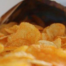 Potato crisps spilling out of a bag.