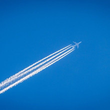 A plane flying across the sky, leaving a streaky contrail cloud behind it
