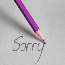 "a purple pencil writing the word ""sorry"" on paper"