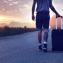 Walking along a road with a suitcase.