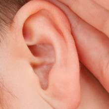 a close up of someone with their hand to their ear, trying to listen