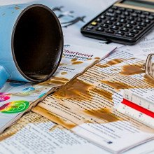 A mug of tea or coffee spilled over some papers.