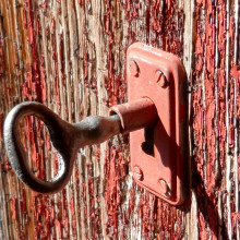 A rustic key partly turned in a lock on a door.