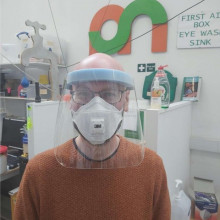 A Makespace volunteer wearing a plastic face visor.