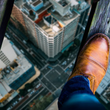 Looking down at a man's shoes as he stands on two thin wooden beams, high above a city street