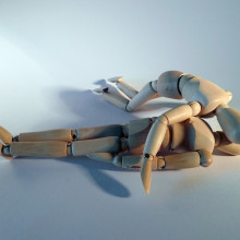 this is a picture of a wooden doll giving CPR to another wooden doll