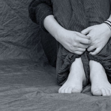 black and white image of someone hugging their knees to their chest