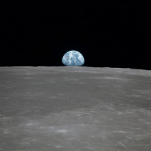 a photo taken from the surface of the moon, looking at Earth as it rises