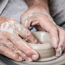 A potter working some clay on a wheel.