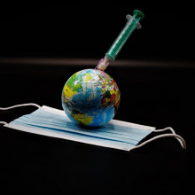 A globe lying on a facemask with a syringe stuck into it.