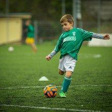 A young boy kicking a football.