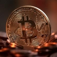 A physical coin imprinted with a Bitcoin logo.
