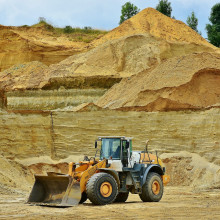 A bulldozer in front of a piled up sand quarry