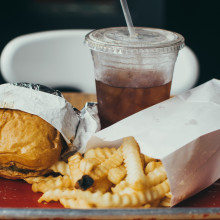 A tray with a burger, chips, and soft drink.
