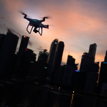 Silhouette of a drone flying over a city