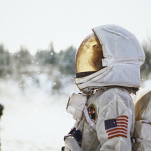 An astronaut in a snowy setting in profile, looking up at the sky
