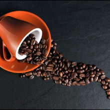 A cup on its side, with coffee beans spilling out of it