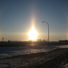 Very bright sun dogs in Fargo, North Dakota. Also visible are parts of the 22° halo (the arcs passing through each sundog), a sun pillar (the vertical line) and the parhelic circle (the horizontal line).