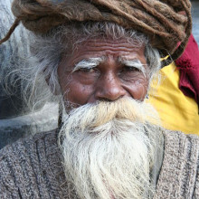 Old sadhu with white beard and coiled dreadlocks in Nepal.