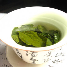 Green tea leaves steeping in an uncovered zhong (type of tea cup).
