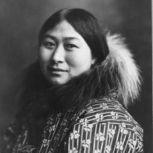 Photograph of an Alaska Native woman wearing a coat with a fur collar.
