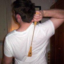 Man scratching back with a Backscratcher